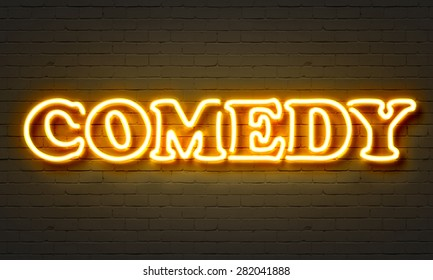 Comedy neon sign on brick wall background