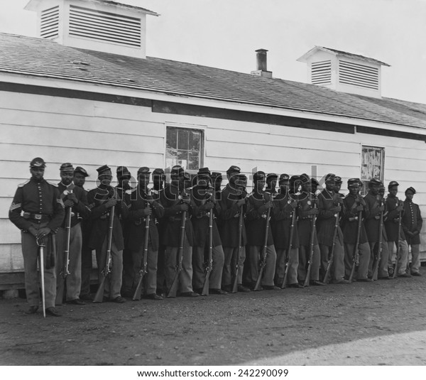 Company E, 4th U.S. Colored Infantry, were part of the defending forces of Washington, D.C. Photo shows two rows of African Americans holding rifles at Fort Lincoln in 1864.