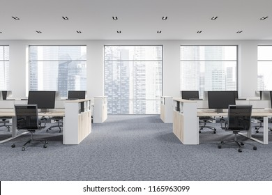 Company office corner with a gray carpet and rows of white computer desks. Industrial style interior with white walls and large windows with a cityscape. Front view. 3d rendering mock up