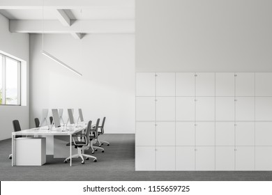 Company office interior with a gray carpet and rows of white computer desks. Industrial style interior with white walls and large windows with tropical view. Lockers on the right 3d rendering mock up