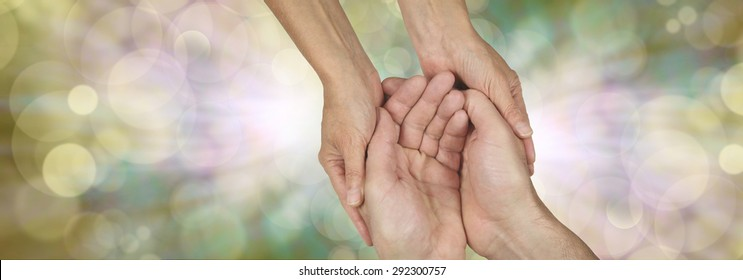 Compassion banner -  wide banner with a woman's hands holding a man's cupped hands in a needy gesture on a bokeh and light burst background and plenty of copy space either side