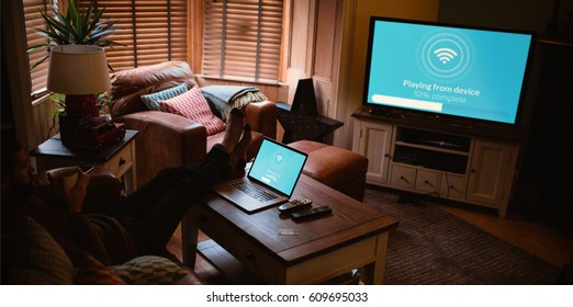Composite image of text with wi-fi symbol against man with laptop on table watching television