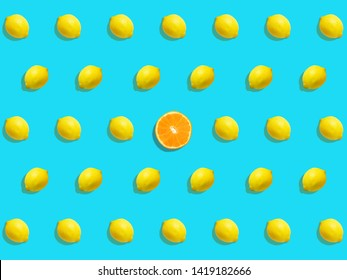 Composite of lemon pattern with a halved orange in the middle on bright blue background
