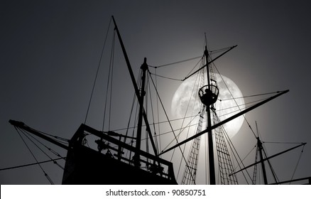 Composition with a silhouette of an old Portuguese caravel in a full moon night.