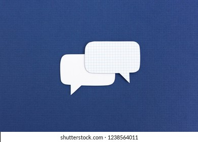 Composition of white paper speech bubbles overlapped on dark blue background
