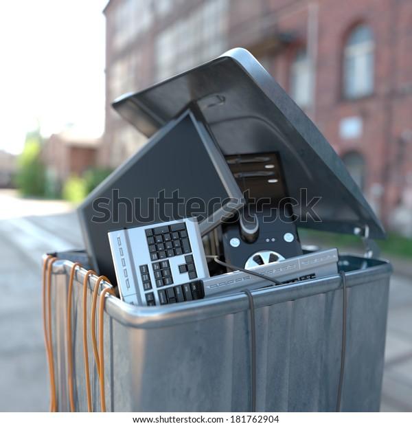 computers in a trash bin on a street