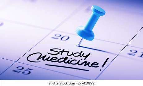 Concept image of a Calendar with a blue push pin. Closeup shot of a thumbtack attached. The words Study Medicine written on a white notebook to remind you an important appointment.