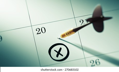 Concept image of a Calendar with a golden dart stick. X mark written on a white notebook to remind you an important appointment.