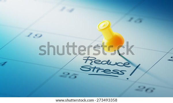 Concept image of a Calendar with a yellow push pin. Closeup shot of a thumbtack attached. The words Reduce Stress written on a white notebook to remind you an important appointment.