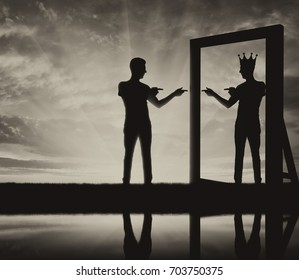 Concept of a narcissistic and egoistic man. Silhouette of a man standing, motivating himself at the mirror and sees in the reflection of himself with a crown on his head