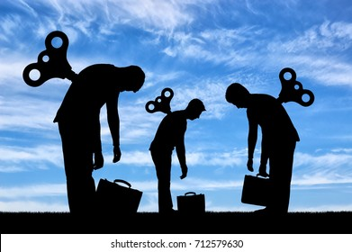 The concept of a tired business team from work. The silhouette of the tired workers with a clockwork mechanism on the back
