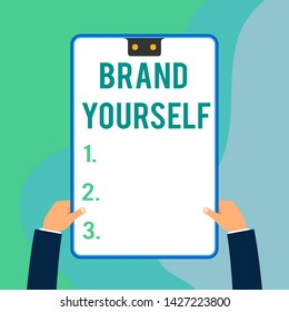 Conceptual hand writing showing Brand Yourself. Business photo text Develop a unique professional identity Personal product Two executive male hands electronic device geometrical background.