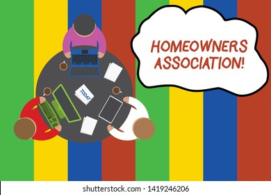 Conceptual hand writing showing Homeowners Association. Business photo showcasing Organization with fee for upkeeps of Gated Community Working table male employees electronic devices coffee cup.