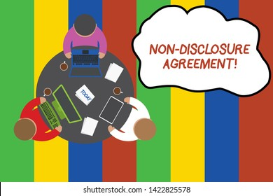 Conceptual hand writing showing Non Disclosure Agreement. Business photo showcasing Legal Contract Confidential Material or Information Working table male employees electronic devices coffee cup.
