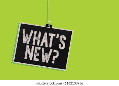 Conceptual hand writing showing What s is New question. Business photo text Asking about latest Updates Trends Happening News Hanging blackboard message communication sign green background.
