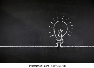 Conceptual idea background with copy space. Lightbulb drawn on black chalkboard. Inspiration and creativity