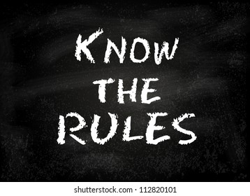 "Conceptual ""Know the rules"" text handwritten on black chalkboard blackboard. Slide template."