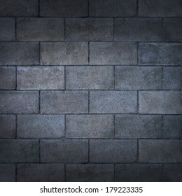 Concrete block wall or weathered cinderblock background with a blank rough rustic cement surface texture as a backdrop of an urban building detail with copy space.