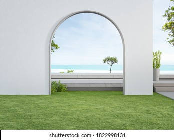 Concrete floor terrace and white wall in luxury hotel or beach house. 3d rendering of arch gate on green grass lawn with sea view.