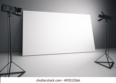 Concrete interior with blank white billboard and professional lighting equipment. Photo studio concept. Mock up, 3D Rendering