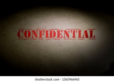 Confidential title on a brown envelope with a light spot.