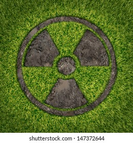 Contaminated soil concept with a green grass and the radio active symbol embossed in the ground exposing the poisoned earth as an icon of environmental disaster after a nuclear disaster fallout.