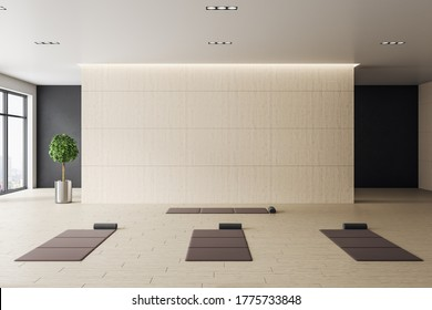 Contemporary interior of yoga classroom with mats and blank wall. Healthy lifestyle concept. Mock up. 3D Rendering