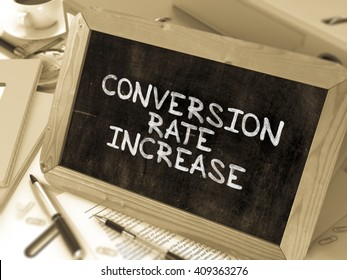 Conversion Rate Increase Handwritten on Chalkboard. Composition with Small Chalkboard on Background of Working Table with Ring Binders, Office Supplies, Reports. Blurred, Toned Image. 3D Render.