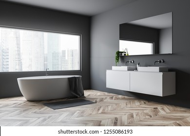 Corner of bathroom with gray walls, wooden floor, white tub standing under big window and double sink on white countertop. 3d rendering