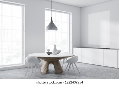 Corner of dining room interior with white walls, concrete floor, loft windows, white countertops with built in cooker and round table with chairs. 3d rendering