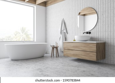 Corner of hotel bathroom with white and tiled walls, concrete floor, comfortable bathtub standing under window and sink on wooden countertop with round mirror. 3d rendering