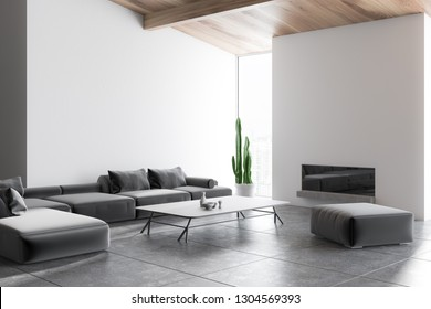 Corner of living room with white walls, tiled floor, long gray sofa standing near coffee table and fireplace. 3d rendering