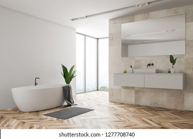 Corner of loft bathroom with white and beige tile walls, wooden floor, large window, bathtub with gray towel on it and white sink standing on white countertop. 3d rendering