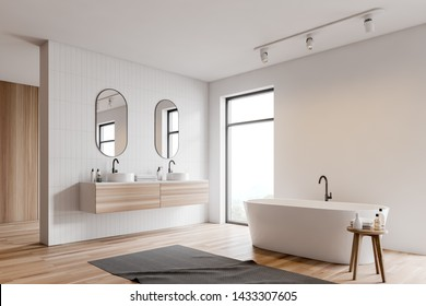 Corner of loft bathroom with white and white tile walls, wooden floor, white bathtub standing near window and double sink with two mirrors above it. 3d rendering
