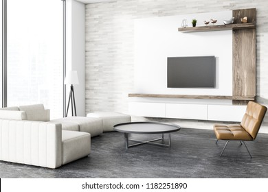 Corner of loft living room with concrete floor, white and wooden walls, a sofa and a leather bench. Round coffee table and a flat TV set on the wall. 3d rendering mock up
