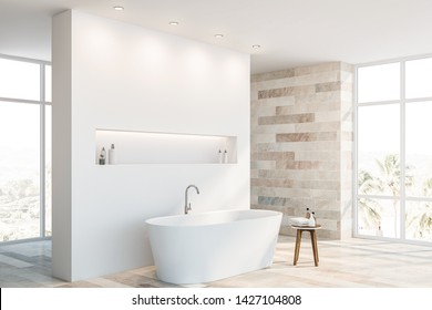 Corner of luxury bathroom with tiled and white walls, white bathtub with shelf above it and small chair with towels and shampoos. 3d rendering
