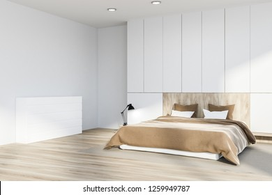 Corner of master bedroom with white walls, wooden floor with a carpet, white and wooden master bed and white closet. 3d rendering
