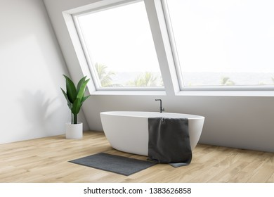 Corner of minimalistic attic bathroom with white walls, wooden floor, white bathtub with towel on it standing under large windows with tropical view. 3d rendering