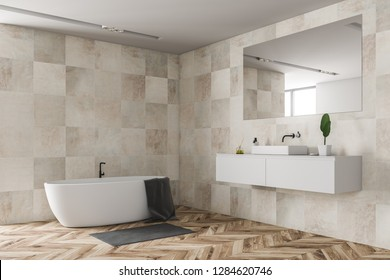 Corner of modern bathroom with beige tile walls, wooden floor, white sink standing on white countertop and white bathtub with towel on it. 3d rendering
