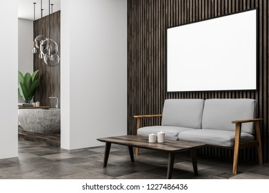 Corner of modern bathroom with dark wooden walls, tiled floor, concrete bathtub, a potted plant and horizontal mock up poster frame on the wall. Gray sofa. 3d rendering