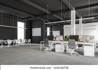 Corner of a modern international company office with dark gray and white walls, and computer desks standing in rows. Industrial style. Pipes. Banners on walls. Meeting room 3d rendering mock up