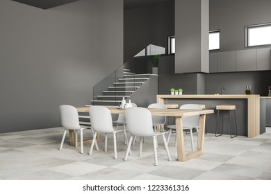 Corner of modern kitchen and dining room with gray walls, tiled floor, gray cupboards, wooden and gray bar, wooden table with white chairs and staircase. 3d rendering