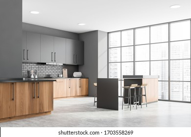 Corner of modern kitchen with gray and brick walls, concrete floor, wooden countertops with built in sink and cooker and grey cupboards. Wooden bar with stools. Blurry cityscape. 3d rendering
