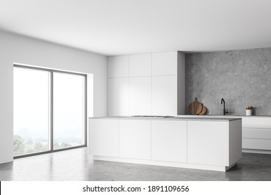 Corner of modern kitchen with white and concrete walls, concrete floor and white island. Cupboards with built in sink and cooker. Window with blurry mountain view. 3d rendering