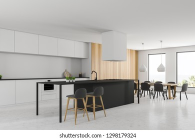 Corner of modern kitchen with white walls, stone floor, white countertops, black bar with stools and long wooden table with gray chairs. 3d rendering