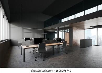 Coin du bureau moderne avec murs gris foncé et en bois, sol en béton, grande fenêtre avec paysage urbain, rangées de tables d'ordinateurs en bois et bureau de réception à droite. Rendu 3d