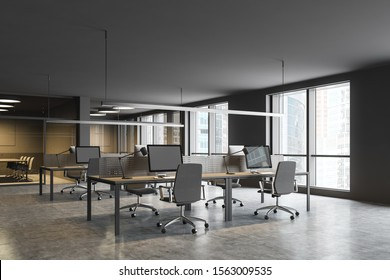 Corner of modern open space office with gray walls, concrete floor, row of gray computer tables and conference rooms in background. 3d rendering