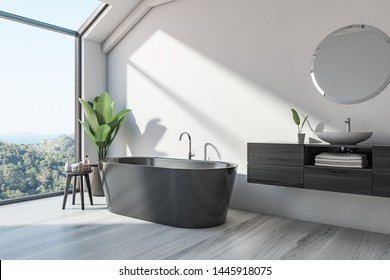 Corner of Scandinalvian style bathroom with white walls, wooden floor, black bathtub and sink standing on wooden countertop with round mirror above it. 3d rendering