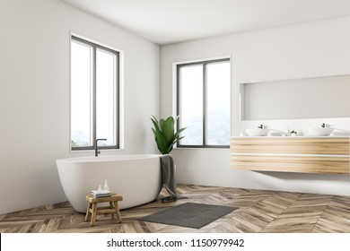 Corner of Scandinavian bathroom interior with white walls, a wooden floor, large windows and a white bathtub standing next to a double sink. 3d rendering mock up