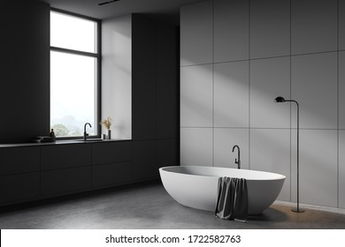 Corner of spacious bathroom with grey walls, concrete floor, comfortable white bathtub and sink near window with blurry mountain view. 3d rendering